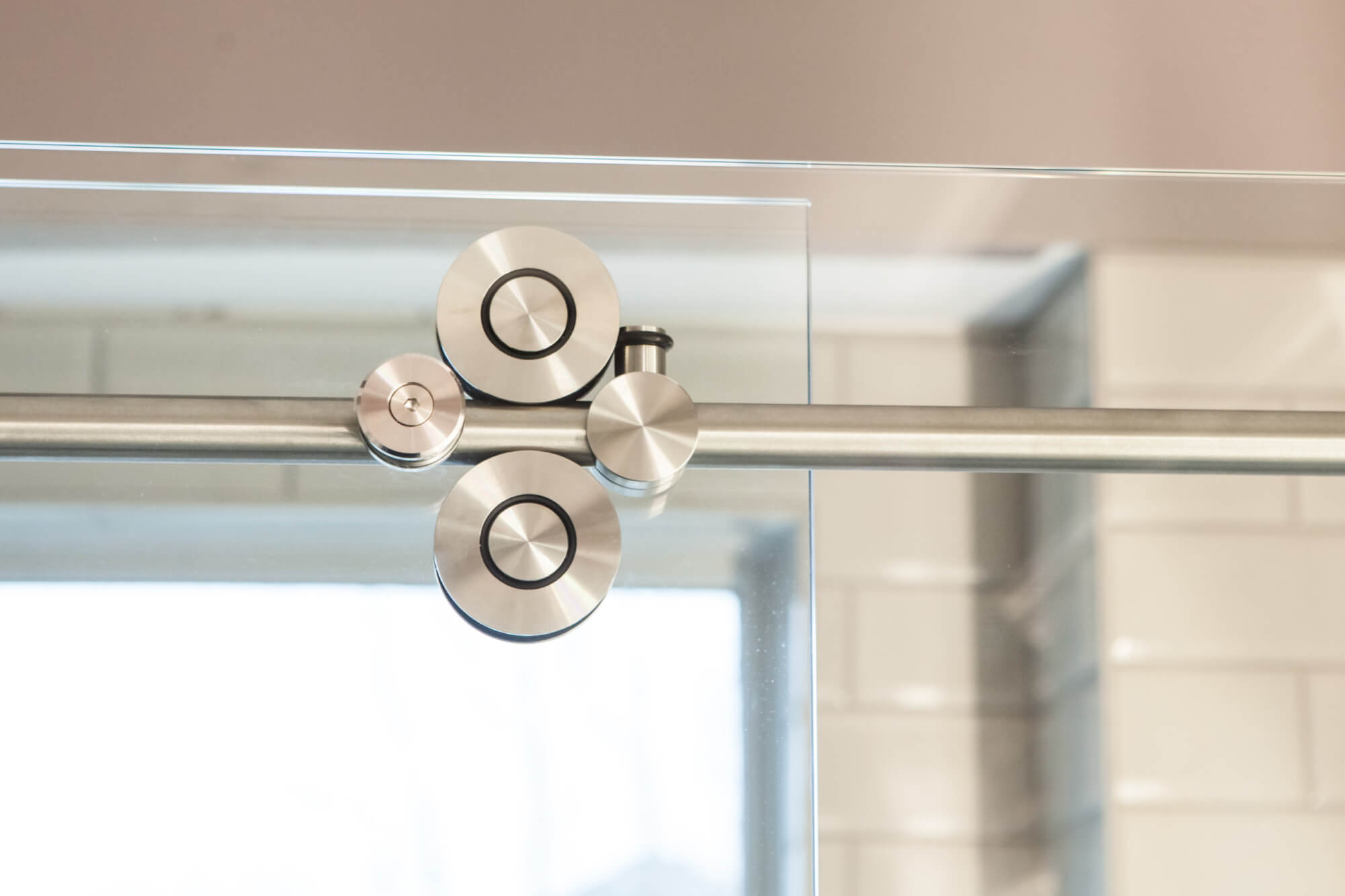 close up of the brushed hardware on a sliding glass shower door