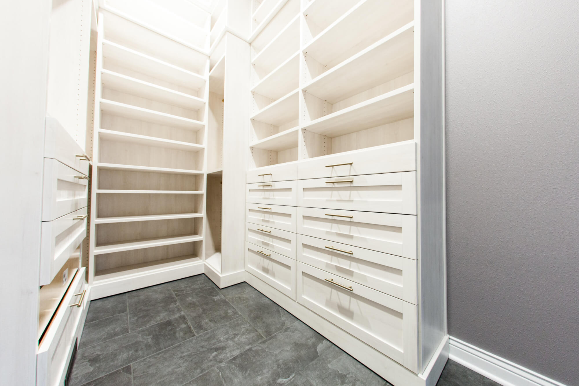 walk-in closet with built in white shelving and a tiled gray floor
