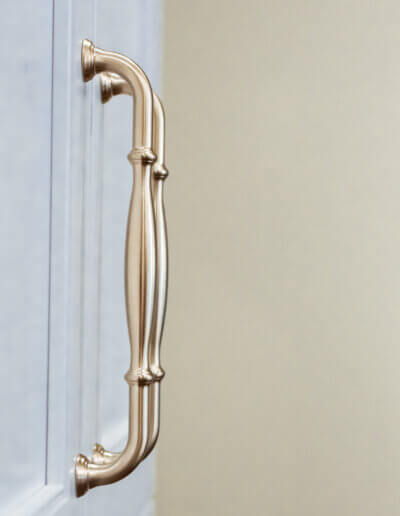 close up photo of white cabinet and brass pulls
