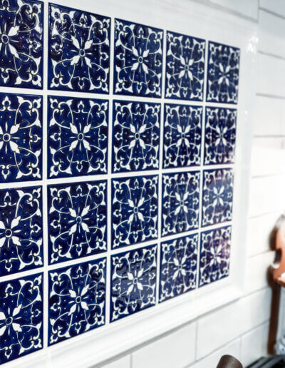up close photo of blue and white tiled backsplash accent above stovetop