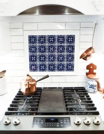 downward shot of black metal stovetop, white and blue tiled backsplash and copper accent utensils