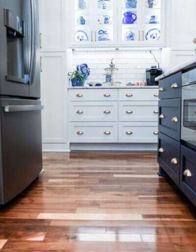 photo from the ground showing shiny mixed hardwood floors, navy gray kitchen island drawers, and white cabinetry down the kitchen
