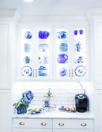 photo of white cabinets with built in white hutch for clue/white china and small marble countertop with miscellaneous kitchen items