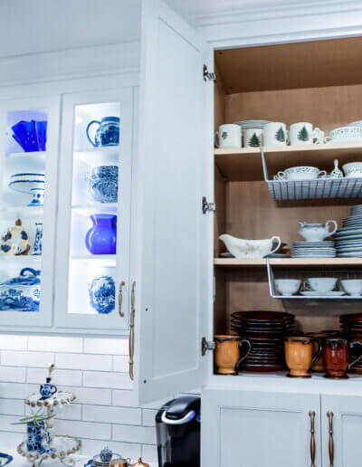 photo of open white cabinet showing interior white dishes and blue/white china shelving next to it