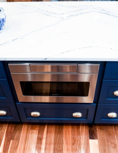 downward view of navy blue kitchen island drawers and built-in silver appliance