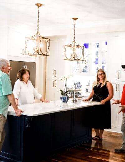 4 people standing around kitchen island talking
