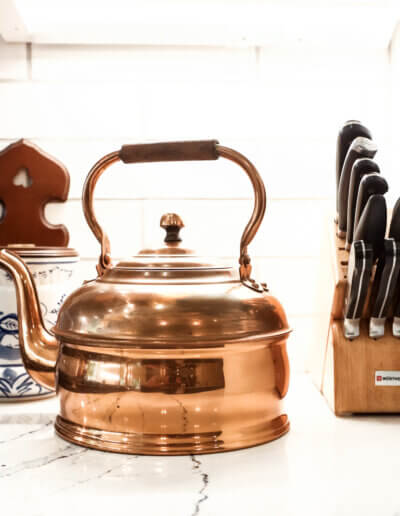 close up image of copper tea kettle on marble countertop between white and blue utensil holder and knife holder