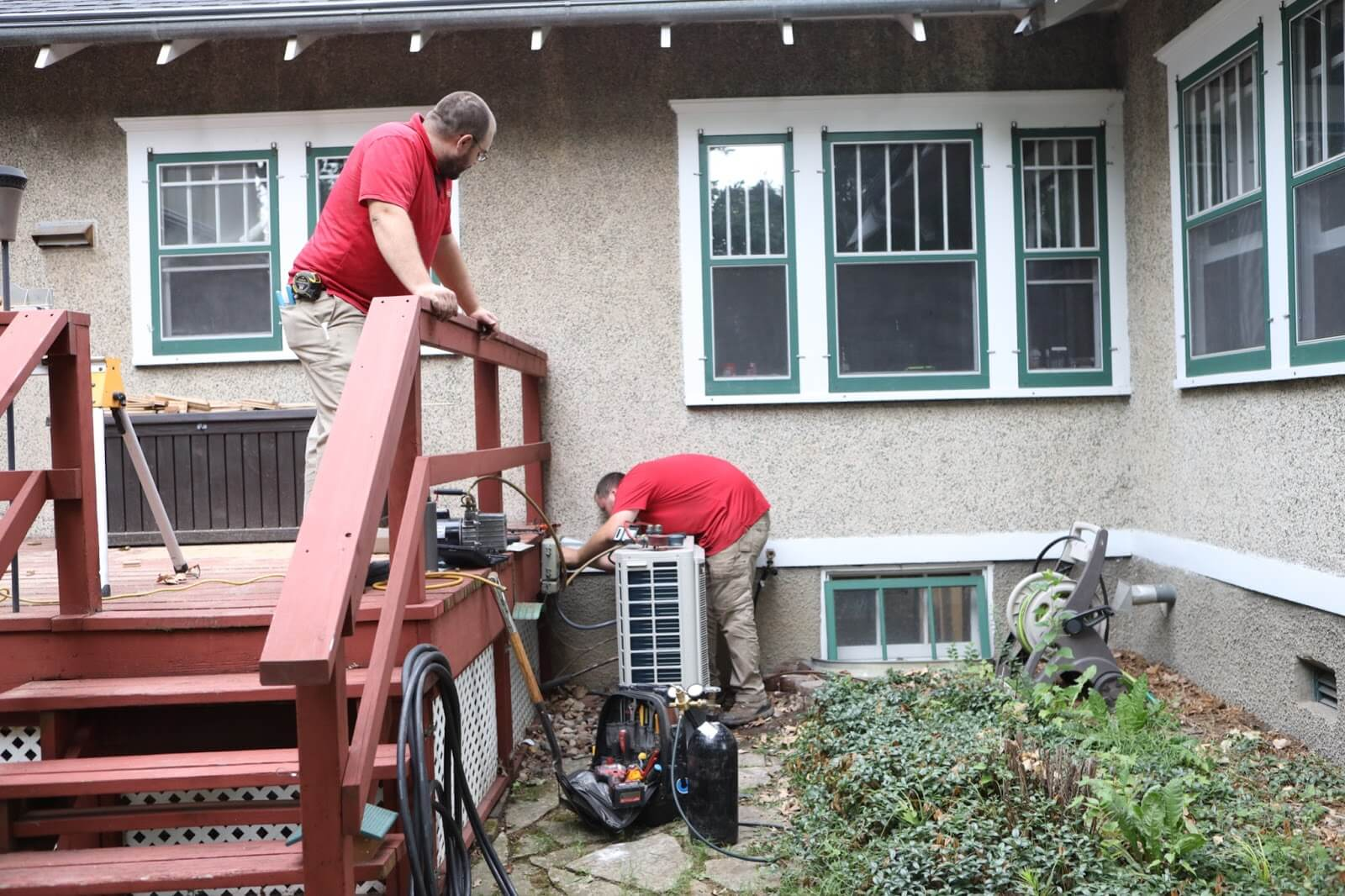 two HVAC technicians from Cyclone Contracting in Ames, IA work on an outdoor AC unit.