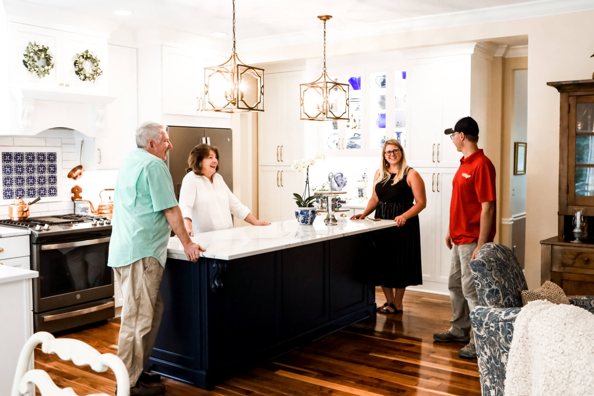 four smiling people stand around newly renovated kitchen and kitchen island