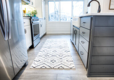 long shot of modern farmstyle kitchen with silver appliances, gray countertops, new light gray laminent with counters facing one another and white/black runner rug