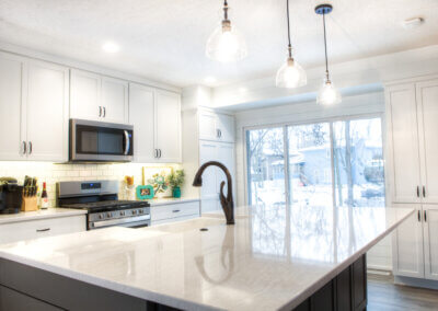 sparkling white kitchen island countertop with deep sink and pendant lighting above, countertop and appliances in the background with white tile backsplash