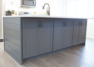 backward shot of gray kitchen island facing out with three cabinets built in