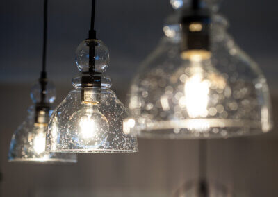 close up detailed photo of glass pendant lights above kitchen island