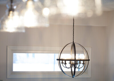close up photo of black metal spherical pendant light above kitchen table