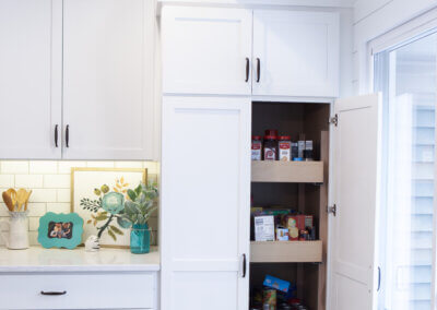 wide shot photo of back kitchen wall showing white cabinetry and pantry door open