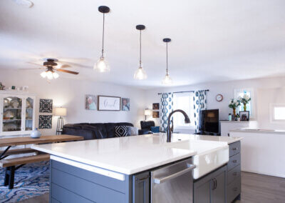 wide shot of kitchen facing out into the common spaces of the dining room and living room