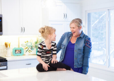 young blonde girl sitting on counter laughing with blonde woman next to her standing and smiling at her