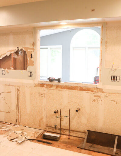 stripped drywall of new construction with plaster on the ground and window looking into next room