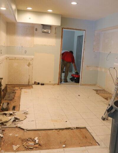 photo into kitchen of stripped drywall, plaster on floor, folded silver ladder against wall and broken white tile