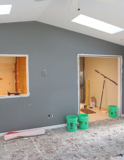 outside photo looking into kitchen under construction of gray wall, stripped flooring and green construction buckets along floor