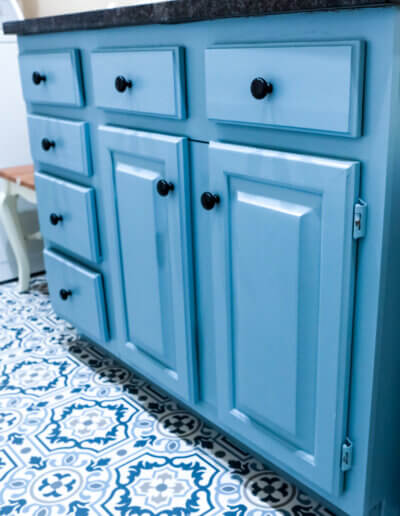 up close photo of blue cabinets under black countertop on right laundry room side wall