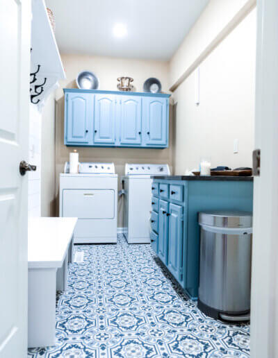 closer shot down into laundry room with white/blue ornate tiled flooring, soft orange walls, teal cabinetry and white washer/dyer