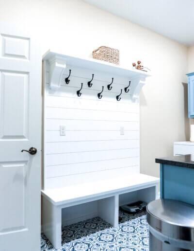 white wooden slated hanging with black hooks, white bench and blue/white ornate tiled floor