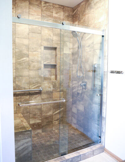 full view of shower with brown tile marbling, clear glass doors shut with silver fixtures