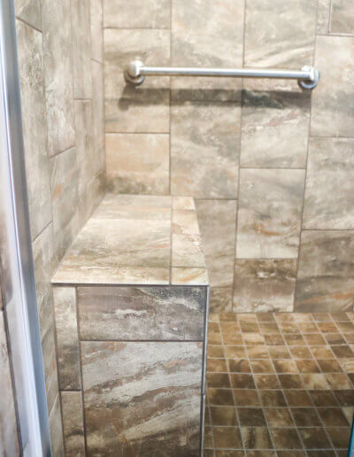 brown and cream marbled tile shower bench along opposite wall of silver shower handle and faucet
