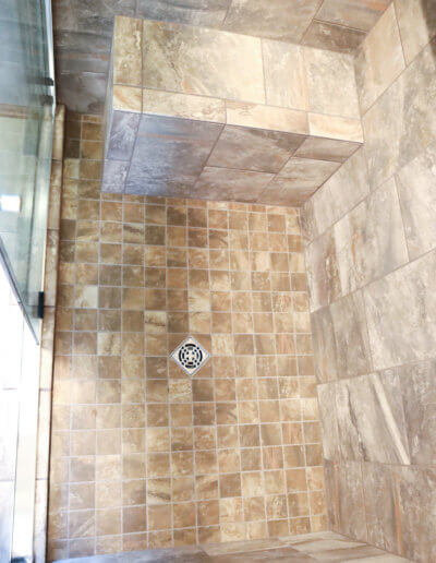 full downward shot into brown tiled shower with silver drain in the middle