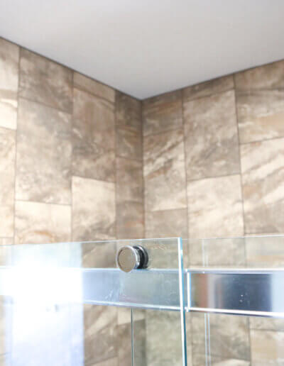 up close top view of shower, with clear glass door and silver accent on bottom of the image and brown tile/ceiling at top of image