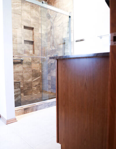 angled photo of bathroom taken from side of the counter, showing the side of dark cherry wood counter across from the brown tiled shower