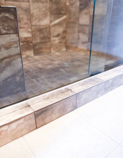 image of floor, cream colored tile meets brown shower tile at a small step into shower