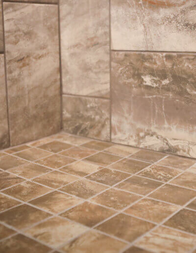 close up image of corner of handicap in-shower seat small brown tile meets large shower wall brown tile