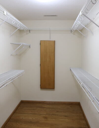 before remodel, looking into closet room with hardwood floors, and white rid racks for hanging and stacking along the walls, a wood panel on the wall facing the door