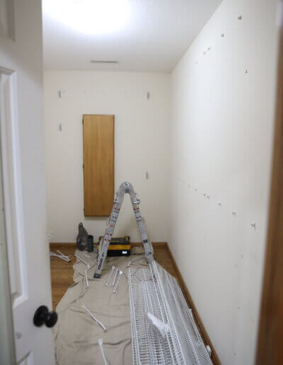 room with hardware for hanging, a dropcloth and small ladder on the floor along with some tools before remodel