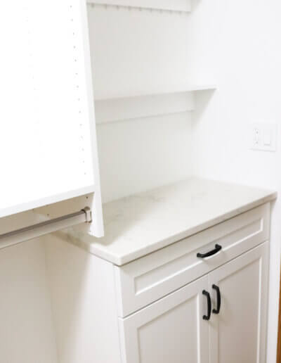 small white countertop with a drawer and two cabinet doors, and two white shelves above it in corner of room