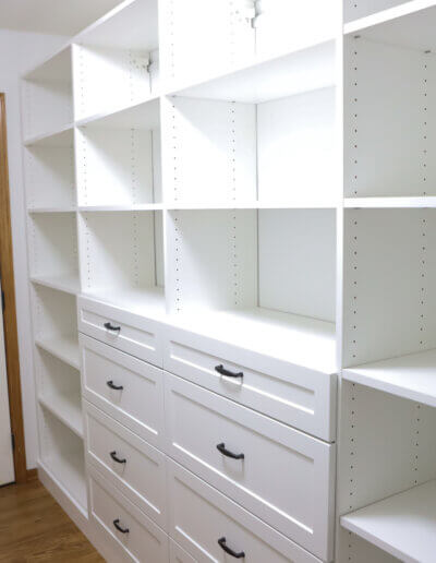 full wall with floor to ceiling empty shelving units with 8 drawers in the middle. A white door at the back of the room next to the shelves