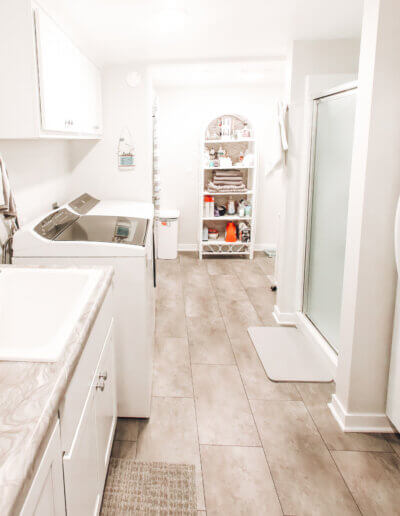 wide shot of complete laundry/bathroom all white with cream and gray marbling countertops/laminent