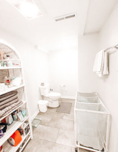 wide shot of toilet in corner with white walls, white rattan shelf and laundry hampers