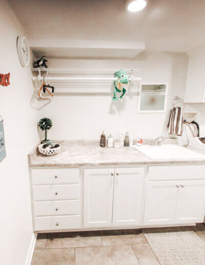 """wide shot of orange metal """"laundry"""" sign and white marble countertop including washer and dryer"""