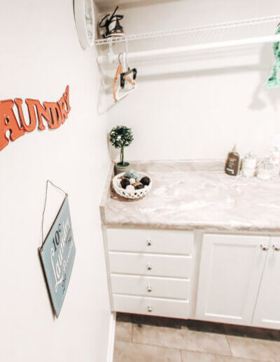 """Orange metal """"laundry"""" sign on wall next to white and gray marble sink countertop"""