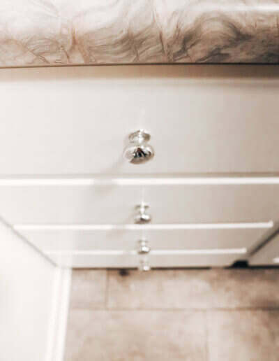 downward view of new white marble drawer with silver knobs