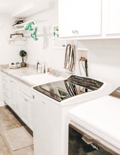 white and black washer and dryer next to gray marble sink countertop and bathroom decor