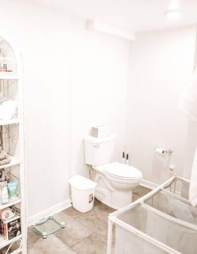 new white toilet in corner next to white rattan shelf and laundry baskets
