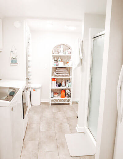 angled photo of laundry and bathroom of white ceiling and walls with clean cream laminent