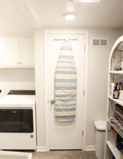 all white walls and ceiling with white appliances and closed door to piping