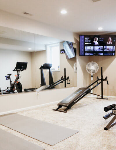 two gray mats facing wall mirror with exercise equipment to the right and tv in the corner of the room