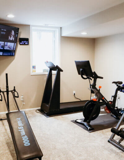 head on shot of black exercise equipment, white fan and tv in the corner