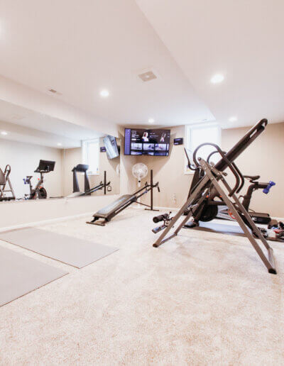 new gym room with two mats, exercise ball, equipment and tv in the corner facing wall mirror